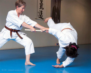 Linda Eskin throwing her partner in an Aikido technique called jo nage - a throw using a wooden staff.